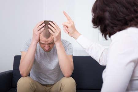 firing: angry employer firing sad employee in modern office