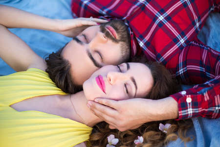 close up portrait of young beautiful couple lying on blanket