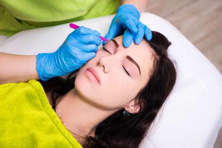 tweezing eyebrow: portrait of young beautiful woman getting tweezing eyebrow by beautician in salon