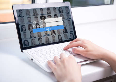 close up of woman using laptop with login box on screen photo