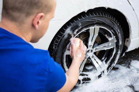 handle carwash concept - back view of young man with sponge washing car wheel