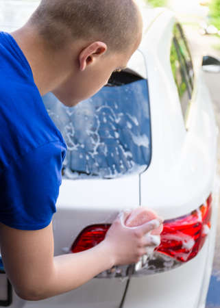 shinning light: back view of young man washing rear lights of car with sponge and soap