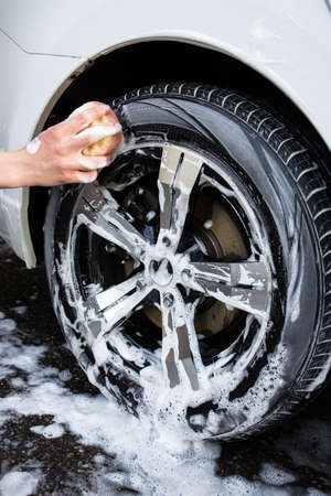 valet: close up of male hand with sponge washing car wheel