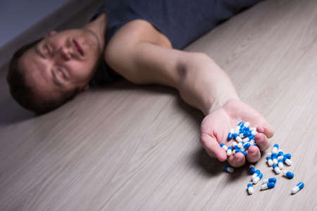 sobredosis: overdose or suicide - young stoned man with pills lying on the floor
