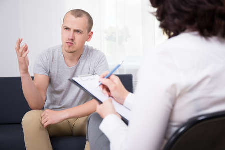 portrait of happy young man talking about something at interview in modern office
