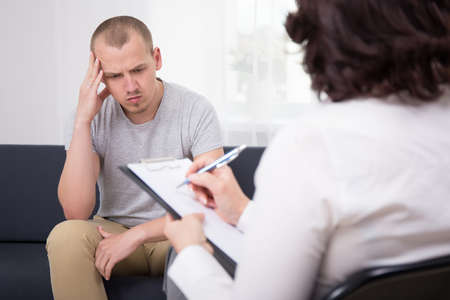 dismiss: sad man listening to employer on interview in office