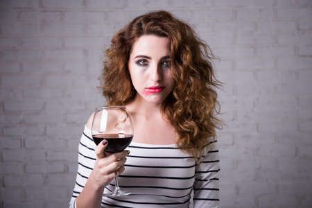 smeared mascara: depression - portrait of sad young woman crying and drinking wine