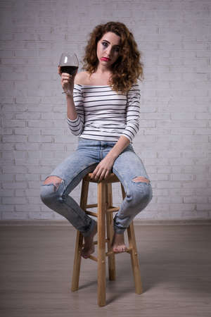 smeared mascara: portrait of crying sad woman with glass of red wine Stock Photo