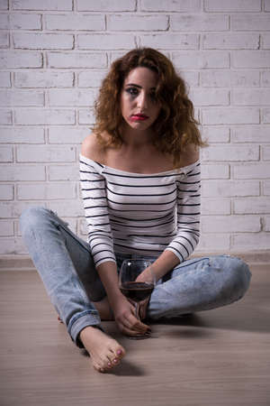 smeared: drunk young woman sitting on the floor with glass of wine Stock Photo