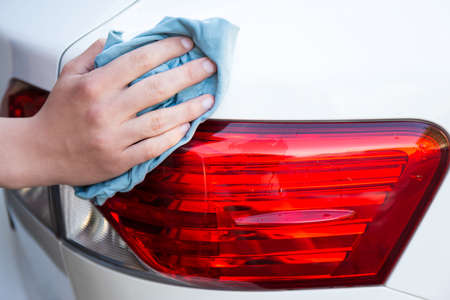 close up of male hand washing car with microfiber cloth