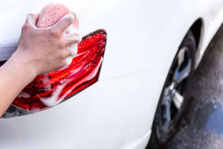 male hand washing car with sponge and soap