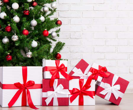 gift boxes under decorated christmas tree with colorful balls stock photo 64573299