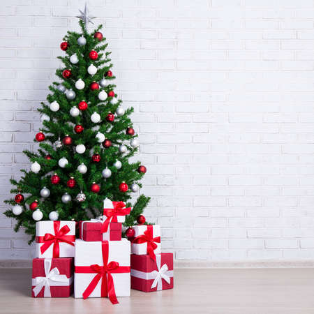 christmas tree with colorful balls and gift boxes over white brick wall