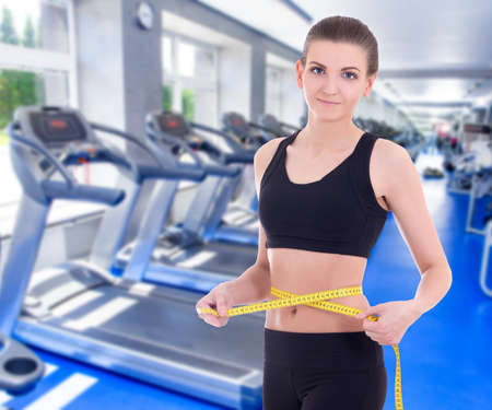 waistline: weight loss concept - beautiful slim sporty woman with measure tape in modern gym Stock Photo