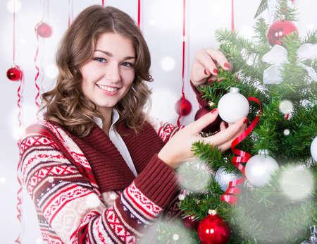 decorating christmas tree: portrait of happy young beautiful woman decorating Christmas tree Stock Photo