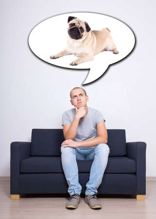 man sitting on sofa and dreaming about dog over white wall