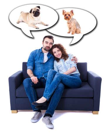 jeune homme et femme assise sur un canapé et rêver de chiens isolés sur fond blanc