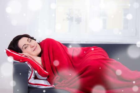 tiredness: winter tiredness - happy mature woman sleeping on sofa at home
