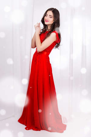show window: winter concept - full length portrait of beautiful woman in red dress standing near the window Stock Photo