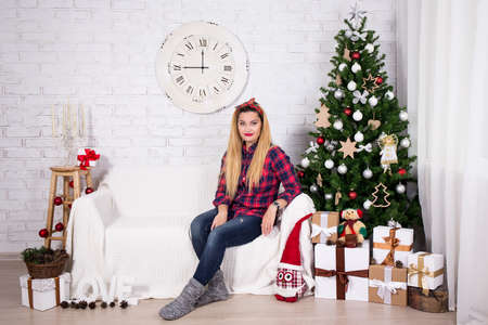 young tree: young woman sitting in decorated living room with christmas tree