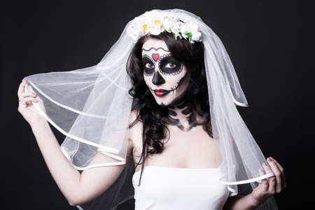 sugar to veil: portrait of beautiful woman bride with creative sugar skull make up and bridal veil over black background