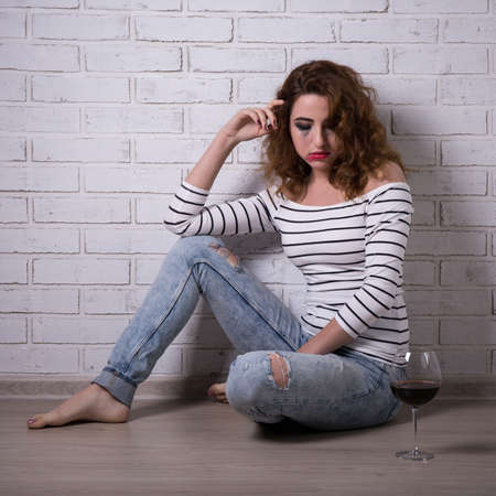 depression and alcoholism - unhappy young woman sitting on the floor with glass of wine