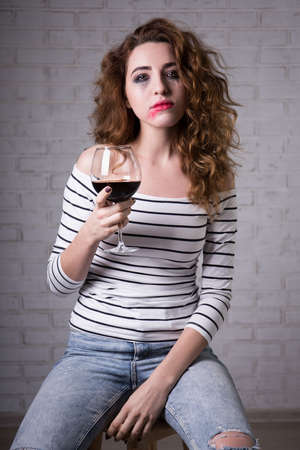 smeared mascara: portrait of sad woman crying and drinking red wine