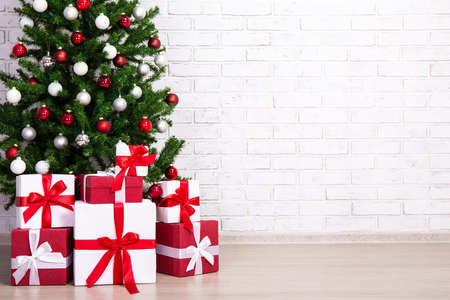 Decorated christmas tree with colorful balls and gift boxes at home