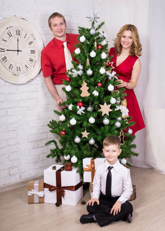 decorating christmas tree: happy parents and little son decorating Christmas tree at home Stock Photo