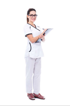 full length portrait of young beautiful woman doctor writing something on clipboard isolated on white background Standard-Bild