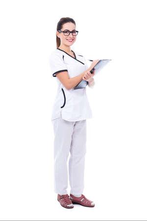 volledige lengte portret van jonge mooie vrouw arts schrijven iets op Klembord geïsoleerd op een witte achtergrond