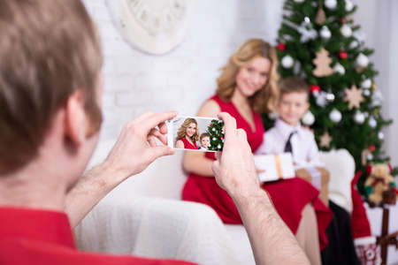 young man taking photo of his wife and son with Christmas tree
