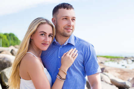 romantic beach: portrait of beautiful couple standing on rocky beach