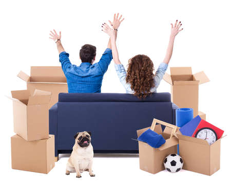 moving day concept - back view of cheerful couple sitting on sofa with brown cardboard boxes and dog isolated on white background