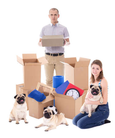 moving day and new home concept - cheerful couple with brown cardboard boxes and dogs isolated on white background Stock Photo