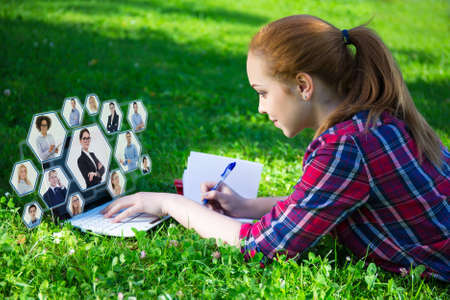 internet and social network concept - teenage girl lying on green in park and using laptop photo