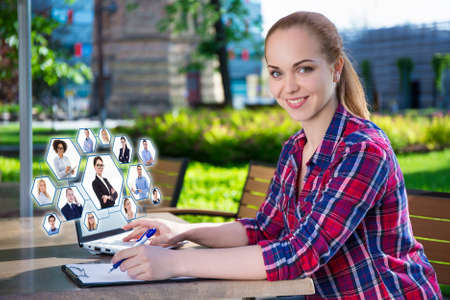internet and social network concept - beautiful teenage girl using laptop in park photo
