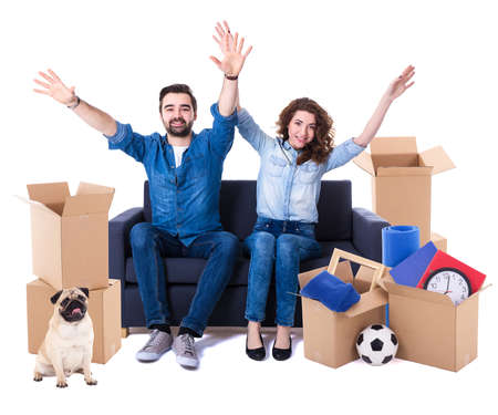 moving day and new home concept - cheerful couple sitting on sofa with brown cardboard boxes and dog isolated on white background Stock Photo