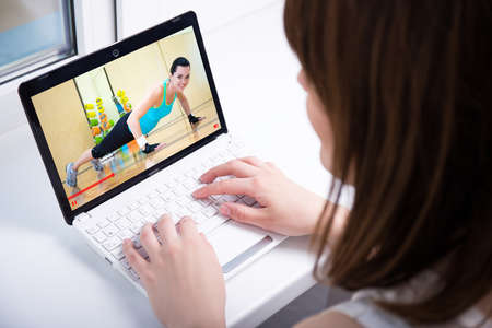 video blog concept - back view of young woman watching on laptop video about sport Standard-Bild