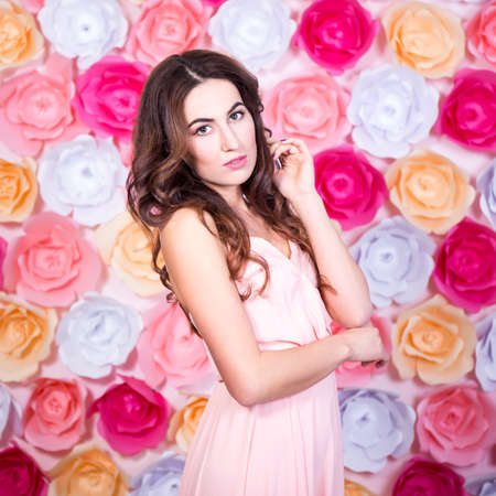 artificial hair: spring and summer concept - portrait of young beautiful woman over colorful paper flowers background