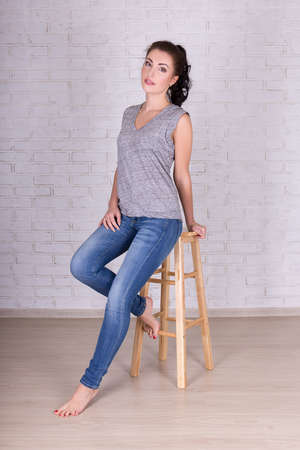 full length portrait of young beautiful woman sitting on wooden chair over white brick wall