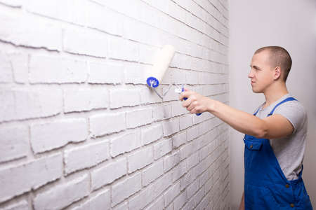 young man painter in uniform painting white brick wall with paint roller