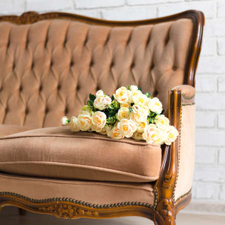 bouquet of rose flowers on ancient vintage sofa