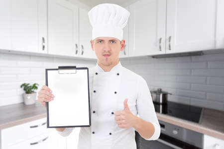 young handsome man in chef uniform thumbs up and showing clipboard with copy space in modern kitchen photo