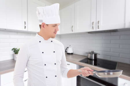 portrait of young handsome man chef in uniform with frying pan in modern kitchen photo