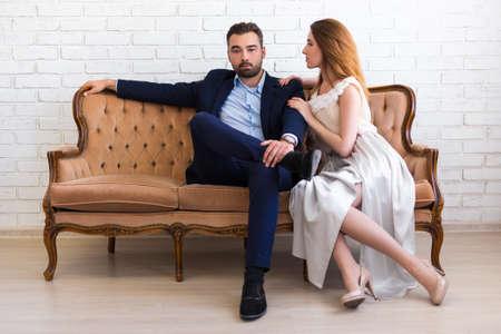 concepto de riqueza y éxito - hombre guapo con barba en traje de negocios sentado en el sofá vintage con hermosa chica