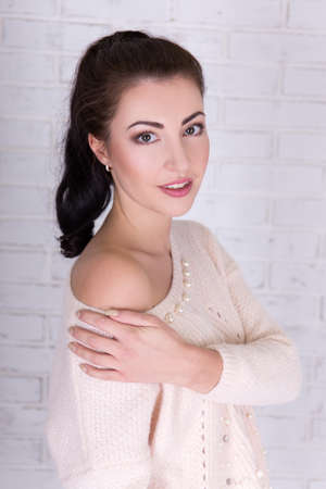 portrait of cute beautiful woman in white sweater over white brick wall photo