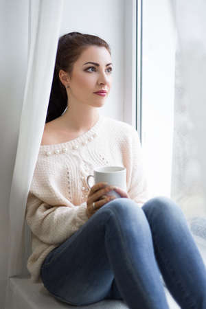 cute young beautiful woman drinking coffee and looking out of the window photo