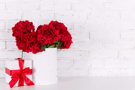 birthday or valentines day background - beautiful red flowers and gift box over white brick wall