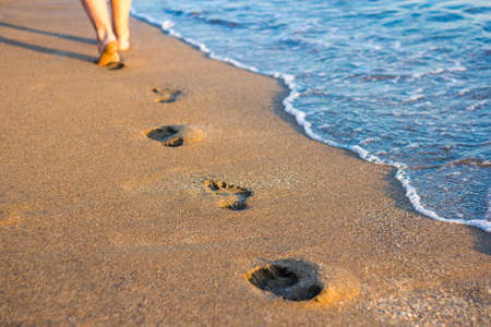 travel and vacation concept - legs, footprints in the sand and sea wave on the beach Banco de Imagens
